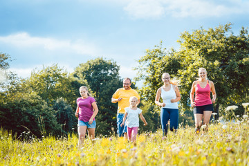 Family running on a meadow with flowers for sport