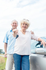 Close-up of the hands of a senior woman showing the keys of her car while posing next to her partner as confident elderly drivers