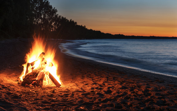 Glowing Bonfire on Beach at Sunset