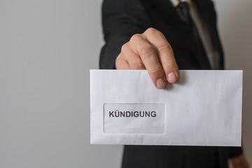Mann hält Brief mit Kündigung