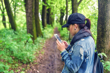 young girl with smartphone in the forest