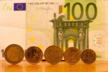 coins of euro and 100 euro banknote in background.