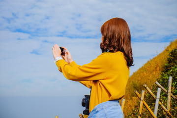 Young asian woman taking a photo with her phone with blue sky background in Thailand
