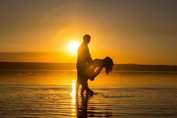 Young couple is dancing in the water on summer beach. Sunset over the sea.Two silhouettes against the sun. Calm and still surface of water. Romantic love story. Man and woman in love in honeymoon trip
