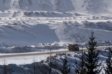 Large ore carrying truck driving through an open pit surface mine in winter