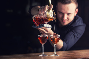 Bartender pouring cocktail alcoholic drink Manhattan.