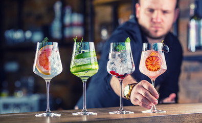 Barman in pub or restaurant preparing a gin tonic cocktail drinks in wine glasses