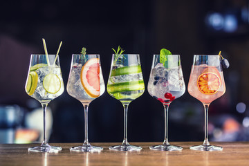 Five colorful gin tonic cocktails in wine glasses on bar counter in pup or restaurant