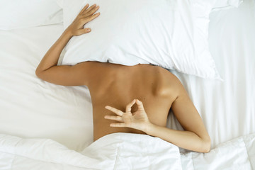 Woman is hiding under the pillow and don't want to wake up