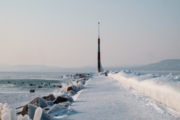 beautiful frozen lake and light tower, port covered by ice, afternoon, Balaton, Hungary, shape of hills in background