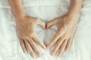 Female hands showing gesture of love