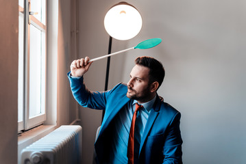 Attractive businessman with fly swatter.