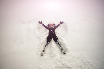 girl lies snow shows  wings angel winter