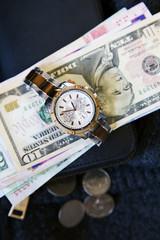 Women's watch, wallet and money cash and coin is on wool. Dollars, yuan, Hong Kong dollars, baht, Lira
