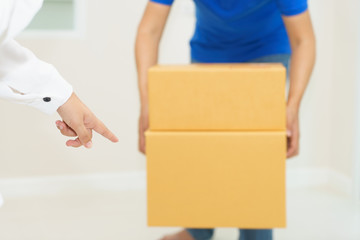 Woman receiving package from delivery man - put it down.