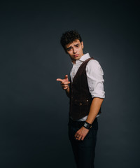 A young, handsome guy posing on a gray studio background. The man is stylish dressed. The guy calls attention and points a finger at the object causing astonishment and disgust