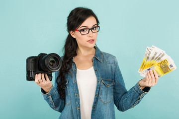 Young woman with camera and cash