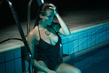Sexy woman in the pool at night