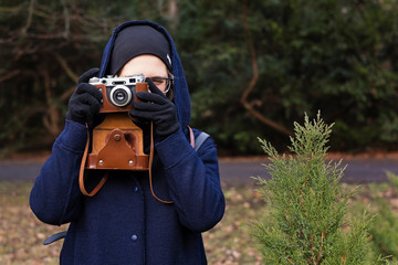 Young woman holding retro photo camera and taking photo in the park. Lifestyle concept with autumn nature on background