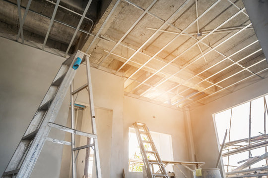 Install metal frame for plaster board ceiling at house under construction