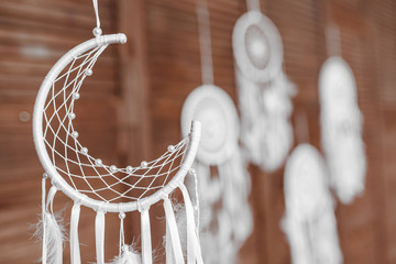 Many Handmade white dream catchers hanging at wooden wall