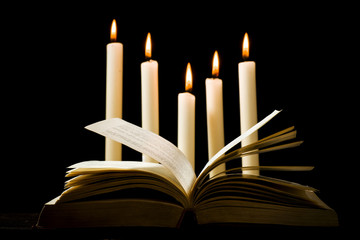 Knowledge concept, open book on a background of candles