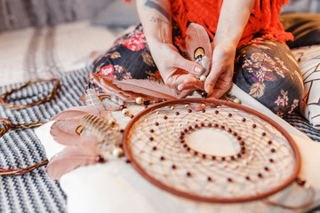 A woman master makes homemade dream catchers as decorations and amulets for the home