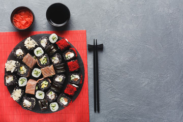 Set of black rolls with chopsticks on gray table