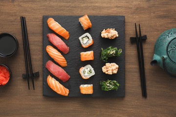 Top view set of sushi maki and rolls near teapot