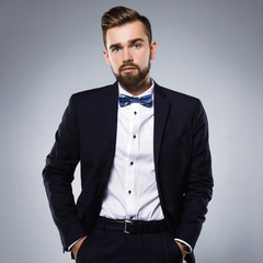 Stylish handsome man wearing a classic suit with bow-tie