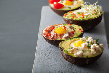 eggs baked in avocado with bacon, cheese, tomato and alfalfa sprouts