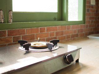 Stove are on a shelf in front of windows.