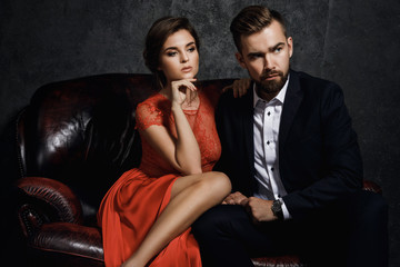 Attractive young couple is sitting on the leather sofa