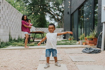 A little boy playing in the yard with his mom & younger sister