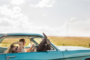 Girl in Passenger seat with legs hanging out the window.