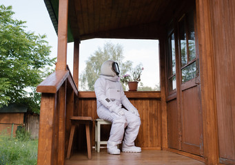 Man sitting on porch in space suit