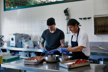 Two cooks working together with good mood and preparing strawberries for a restaurant kitchen