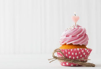 pink cupcake on white wooden background