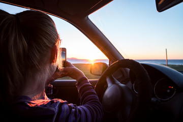 Young women take picture of the sunset from car
