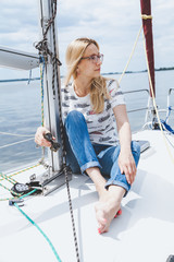 slender barefooted blonde in spectacles sits on nose of yacht