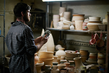 Talented potter looking at his work in small dim ceramics shop