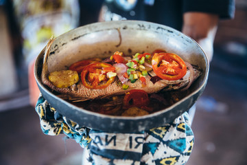 Local African fried fish dish being served with vegetables