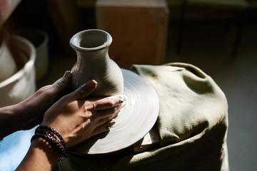 Gentle hands of female potter working on throwing wheel in sunli