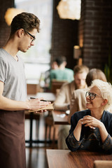 Cheerful woman ordering lunch in cafe