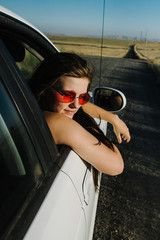 teenager wearing red sunglasses leans out car window on country road