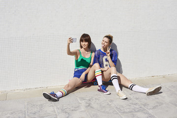 Portrait of two young women with skateboards making a selfie
