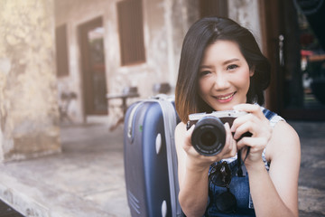 beautiful asian woman short hair travel with casual dress and camera with happiness color tone filter effect