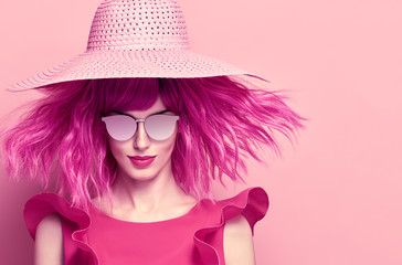 Glamour Beautiful Lady. Party fashionable Hairstyle. Fashion woman in pink Summer Dress. Young Playful female model with Pink Hair in Stylish fashion Hat. Trendy Sunglasses.