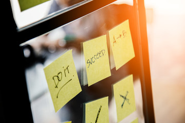yellow paper note pad stick on office window business ideas concept