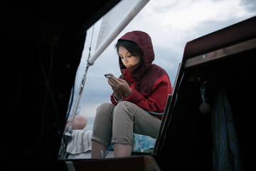 Yougn woman with smartphone on boat